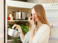 Woman holding her nose because of bad smell long haired near fridge at home Royalty Free Stock Images