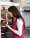 Woman holding her nose because of bad smell near fridge brunnette at home Stock Image