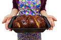 Woman holding home made freshly baked traditional romanian Christmas Xmas sponge cake cozonac still in baking form. Royalty Free Stock Photo
