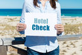 Woman holding hotel check sign at beach midsection of Stock Photos