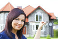 Woman holding keys with house background Royalty Free Stock Photo