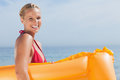 Woman holding lilo smiling at camera on beach Stock Photography
