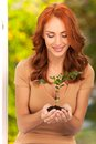 Woman holding little plant in her hands. Royalty Free Stock Photo