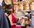 Woman holding mirror and showing customer his reflection in hats Royalty Free Stock Photo