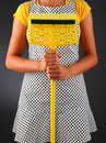 Woman holding a mop closeup of homemaker in an apron sponge in front of her torso vertical format over light to dark background Stock Photo