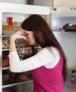 Woman holding nose because of bad smell from food brunnette her near refrigerator at home Royalty Free Stock Photos