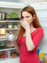 Woman holding nose because of bad smell near fridge at home Stock Image