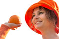 Woman holding the oranges isolated in orange hat Stock Photo