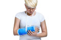 Woman holding painful broken arm young in blue cast on a white background Stock Images