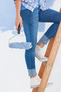 Woman holding paint roller climbing ladder against half painted wall Stock Photography