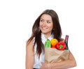 Woman holding a paper shopping bag full of groceries happy young salad green pepper tomatoes orange bottle wine isolated on Royalty Free Stock Images