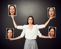 Woman holding pictures with different mood serious young Royalty Free Stock Image