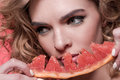 Woman holding piece of grapefruit isolated on pink Royalty Free Stock Photo