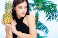 Woman holding pineapple in front of a palm tree Stock Images