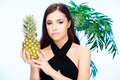 Woman holding pineapple pretty in front of a palm tree Stock Images