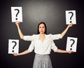 Woman holding placards with question mark serious four hands Stock Photos