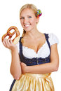 Woman holding pretzel in dirndl smiling happy a a Stock Photos