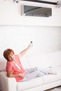 Woman holding a remote control air conditioner at home happy mature on sofa Stock Photography