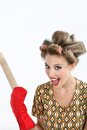 Woman holding rolling pin portrait of pretty young with hair curlers screaming out while over white background Royalty Free Stock Images