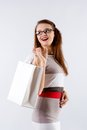 Woman holding shopping white bag young smiling in glasses with on a background Royalty Free Stock Images
