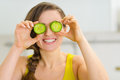 Woman holding slices of cucumber in front of eyes Royalty Free Stock Photo