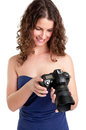 Woman holding an slr camera and looking at the picture she took isolated in white Royalty Free Stock Photo