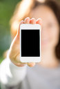 Woman holding smart phone hand against green spring background Royalty Free Stock Photo