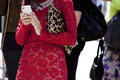 A woman holding smartphone wearing lace red dress Royalty Free Stock Photo