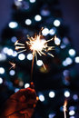 Woman holding sparkler with Christmas tree glitter Royalty Free Stock Photo