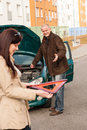 Woman holding triangle sign repairman fixing car Royalty Free Stock Photos