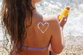Woman is holding tube with sunscreen spf filtred pretty sitting on the sea coast lotion on her back Stock Photos