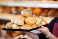 Woman holding various bread rolls in a bakery female worker Royalty Free Stock Photography