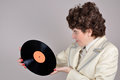 Woman holding a vinyl record pleasantly surprised and looking at vintage style photo Stock Photos