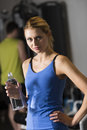 Woman holding water bottle at health club portrait of confident young women with men in background Stock Images