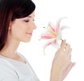 Woman holding a white lily at face isolated over beautiful young Stock Photography