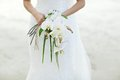 Woman holding white orchid wedding bouquet with beach background Royalty Free Stock Photo