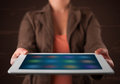 Woman holding a white tablet with blurry apps young Royalty Free Stock Images