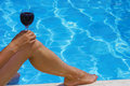 Woman holding wine on her knee at the poolside Stock Photography