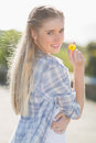 Woman holding yellow flower in hand smiling at camera Royalty Free Stock Images
