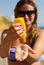 Woman is holding yellow tube with sunscreen tan pretty lotion and putting cream to hand Stock Images