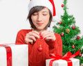 Woman holds christmas red ball young in santa hat is holding a on a background of tree Royalty Free Stock Images