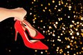 Woman holds fashionable red shoes in her hand on defocused abstract Christmas party background. Royalty Free Stock Photo