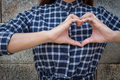 Woman holds heart shape on own