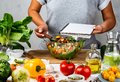 Woman holds recipe book with place for text in her hand and cooking healthy food in the kitchen. Healthy vegan food