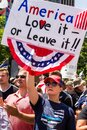 A Woman Holds a Sign Reading `America Love it Or Leave it` at a Conservative Rally Royalty Free Stock Photo
