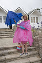 Woman at a holiday location opening an umbrella holidaymaker with and poncho the seaside on wet day Royalty Free Stock Photography