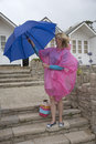 Woman at a holiday location opening an umbrella holidaymaker with and poncho the seaside on wet day Royalty Free Stock Image