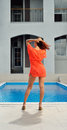 Woman at the home pool a young is standing outdoor swimming in yard of her house Stock Photos