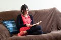 Woman at home reading book on couch Stock Photos