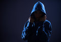 Woman with hood in darkness Stock Photo